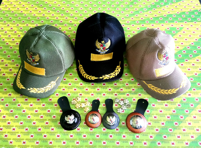 dari kiri ke kanan: Topi lurah, topi bupati, topi camat bagian tengah terdapat melati untuk tanda jabatan yang dipasang pada topi jaring, dan bagian bawah adalah tanda pangkat jabatan